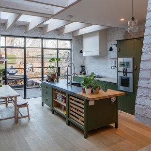 Scandinavian single-wall open plan kitchen in London with a double-bowl sink, shaker cabinets, green cabinets, limestone benchtops, white splashback, brick splashback, panelled appliances, medium hardwood floors and with island.
