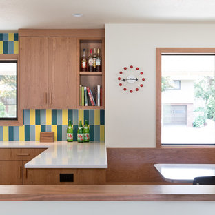 Large midcentury u-shaped eat-in kitchen in Portland with an undermount sink, flat-panel cabinets, medium wood cabinets, multi-coloured splashback, ceramic splashback, stainless steel appliances, light hardwood floors, a peninsula, white benchtop and recycled glass benchtops.