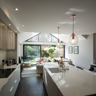 Small modern open plan kitchen with an integrated sink, flat-panel cabinets, white cabinets, composite countertops, white splashback, glass sheet splashback, stainless steel appliances, plywood flooring, an island, brown floors and white worktops.