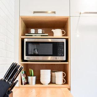 モントリオールの小さい北欧スタイルのおしゃれなキッチン (アンダーカウンターシンク、フラットパネル扉のキャビネット、白いキャビネット、珪岩カウンター、白いキッチンパネル、セラミックタイルのキッチンパネル、シルバーの調理設備、無垢フローリング、オレンジの床) の写真