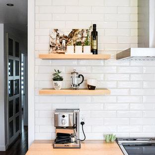 モントリオールの小さい北欧スタイルのおしゃれなキッチン (アンダーカウンターシンク、フラットパネル扉のキャビネット、白いキャビネット、珪岩カウンター、白いキッチンパネル、セラミックタイルのキッチンパネル、シルバーの調理設備の、無垢フローリング、オレンジの床) の写真