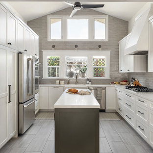 Mid-sized transitional kitchen inspiration - Example of a mid-sized transitional u-shaped porcelain tile and gray floor kitchen design in San Diego with a farmhouse sink, shaker cabinets, white cabinets, quartz countertops, gray backsplash, ceramic backsplash, stainless steel appliances, an island and white countertops