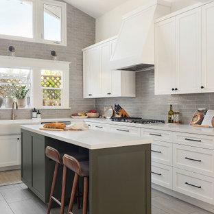 Idéer för mellanstora amerikanska vitt kök, med en rustik diskho, skåp i shakerstil, vita skåp, bänkskiva i kvarts, grått stänkskydd, stänkskydd i keramik, rostfria vitvaror, klinkergolv i porslin, en köksö och grått golv