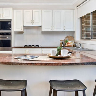 This is an example of a small transitional u-shaped open plan kitchen in Sydney with cement tiles, with island and pink floor.
