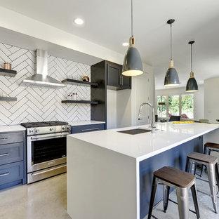 オースティンの小さいモダンスタイルのおしゃれなキッチン (アンダーカウンターシンク、シェーカースタイル扉のキャビネット、青いキャビネット、人工大理石カウンター、白いキッチンパネル、セラミックタイルのキッチンパネル、シルバーの調理設備、コンクリートの床) の写真