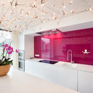 Bild på ett funkis linjärt kök och matrum, med rosa stänkskydd och glaspanel som stänkskydd