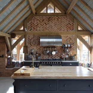 Mid-sized farmhouse kitchen ideas - Inspiration for a mid-sized farmhouse single-wall concrete floor and gray floor kitchen remodel in Other with a farmhouse sink, flat-panel cabinets, blue cabinets, red backsplash, brick backsplash, an island, wood countertops, stainless steel appliances and beige countertops