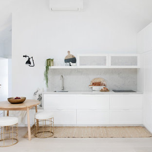 Design ideas for a beach style l-shaped open plan kitchen in Sydney with a single-bowl sink, shaker cabinets, white cabinets, white appliances, no island, grey splashback, light hardwood floors, beige floor and grey benchtop.