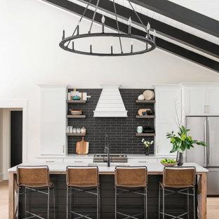 На фото: большая прямая кухня в стиле кантри с врезной раковиной, белыми фасадами, черным фартуком, техникой из нержавеющей стали, светлым паркетным полом, островом, коричневым полом, белой столешницей и сводчатым потолком с