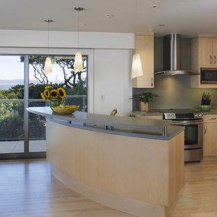 Idee per una cucina contemporanea di medie dimensioni con elettrodomestici in acciaio inossidabile, ante lisce, ante in legno chiaro, top in quarzo composito, lavello sottopiano, paraspruzzi verde, parquet chiaro, isola e paraspruzzi in lastra di pietra