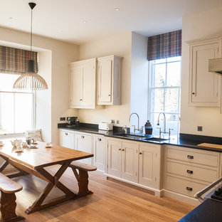 This is an example of a farmhouse l-shaped kitchen/diner in Wiltshire with a submerged sink, recessed-panel cabinets, white cabinets, light hardwood flooring and no island.