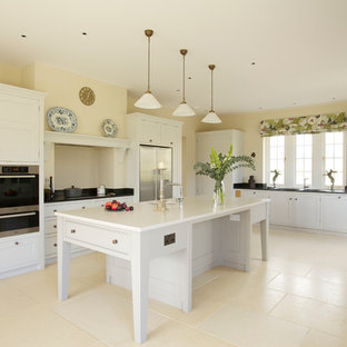 Photo of a large rural u-shaped kitchen in Wiltshire with a submerged sink, shaker cabinets, white cabinets, stainless steel appliances, an island and beige floors.
