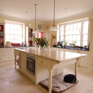 Example of a country u-shaped kitchen design in Wiltshire with an undermount sink, beige cabinets and an island