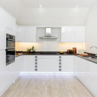 ドーセットのコンテンポラリースタイルのおしゃれなコの字型キッチン (アンダーカウンターシンク、フラットパネル扉のキャビネット、白いキャビネット、人工大理石カウンター、アイランドなし) の写真