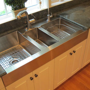 Traditional kitchen in Chicago with a triple-bowl sink, raised-panel cabinets and white cabinets.