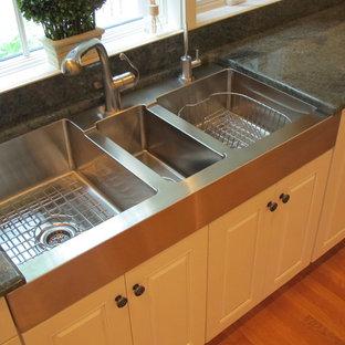 Modelo de cocina clásica con fregadero de tres senos, armarios con paneles con relieve y puertas de armario blancas