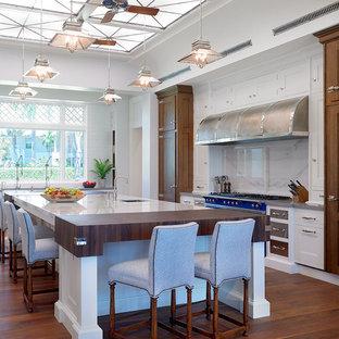 Immagine di una cucina tropicale con lavello sottopiano, ante con riquadro incassato, ante bianche, paraspruzzi bianco, elettrodomestici colorati, parquet scuro, isola, top in marmo e paraspruzzi in marmo