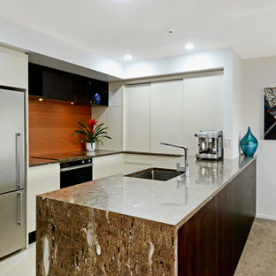 Contemporary kitchen ideas - Inspiration for a contemporary u-shaped porcelain floor and beige floor kitchen remodel in Auckland with an undermount sink, white cabinets, granite countertops, orange backsplash, glass sheet backsplash, black appliances and brown countertops