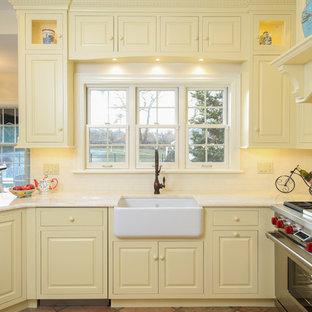 プロビデンスの中サイズのトラディショナルスタイルのおしゃれなキッチン (エプロンフロントシンク、レイズドパネル扉のキャビネット、黄色いキャビネット、御影石カウンター、白いキッチンパネル、サブウェイタイルのキッチンパネル、シルバーの調理設備の、テラコッタタイルの床、アイランドなし、赤い床) の写真