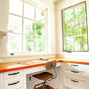 This is an example of a mid-sized traditional u-shaped eat-in kitchen in Vancouver with an undermount sink, shaker cabinets, white cabinets, blue splashback, ceramic splashback, stainless steel appliances, medium hardwood floors, with island, brown floor, wood benchtops and orange benchtop.