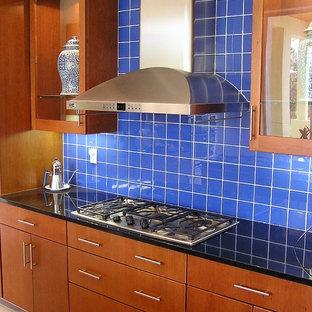 Immagine di una cucina minimalista di medie dimensioni con lavello sottopiano, ante lisce, ante marroni, top in granito, paraspruzzi blu, paraspruzzi in gres porcellanato, elettrodomestici in acciaio inossidabile, pavimento in pietra calcarea, isola e pavimento beige