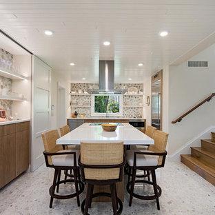 マイアミのトロピカルスタイルのおしゃれなアイランドキッチン (フラットパネル扉のキャビネット、中間色木目調キャビネット、マルチカラーのキッチンパネル、シルバーの調理設備の、テラゾの床、マルチカラーの床、白いキッチンカウンター) の写真