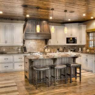 Diseño de cocina en L, rural, con fregadero bajoencimera, armarios con rebordes decorativos, puertas de armario beige, salpicadero beige, electrodomésticos con paneles, suelo de madera en tonos medios, una isla y suelo naranja