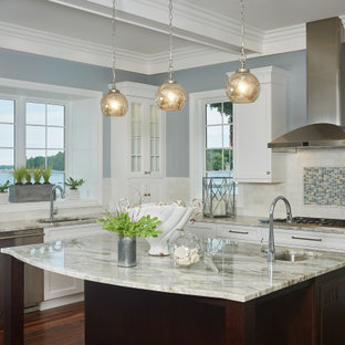 This is an example of a mid-sized beach style l-shaped kitchen in Grand Rapids with recessed-panel cabinets, white cabinets, granite benchtops, white splashback, mosaic tile splashback, stainless steel appliances, medium hardwood floors, with island, white benchtop and coffered.