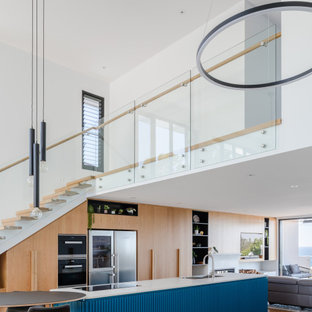 This is an example of a contemporary galley open plan kitchen in Wollongong with an undermount sink, flat-panel cabinets, medium wood cabinets, medium hardwood floors, with island, brown floor and white benchtop.