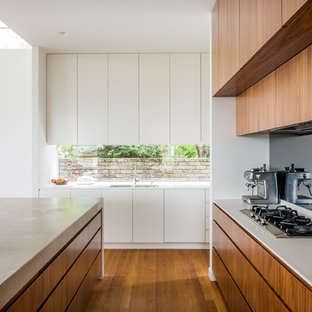 This is an example of a contemporary l-shaped kitchen in Sydney with medium wood cabinets, medium hardwood floors, with island, a double-bowl sink, flat-panel cabinets, window splashback, stainless steel appliances, brown floor and white benchtop.