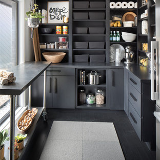 Huge transitional kitchen pantry appliance - Example of a huge transitional single-wall dark wood floor and black floor kitchen pantry design in Indianapolis with flat-panel cabinets, black cabinets, solid surface countertops, stainless steel appliances and an island
