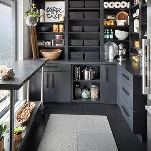 Inspiration pour une très grand arrière-cuisine traditionnelle en L avec un placard à porte plane, des portes de placard noires, un plan de travail en surface solide, un électroménager en acier inoxydable, un sol en bois foncé, un îlot central et un sol noir.