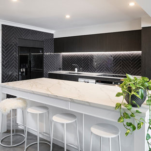 Photo of a mid-sized contemporary galley kitchen in Perth with an undermount sink, flat-panel cabinets, dark wood cabinets, black splashback, subway tile splashback, black appliances, cement tiles, with island, grey floor, white benchtop and marble benchtops.