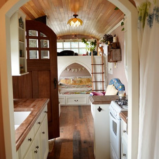 Design ideas for a small arts and crafts galley open plan kitchen in Seattle with an undermount sink, open cabinets, white cabinets, wood benchtops, coloured appliances, medium hardwood floors and no island.