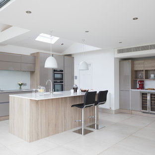 Inspiration for a contemporary kitchen in Other with flat-panel cabinets, beige cabinets, white splashback, an island, beige floors and white worktops.