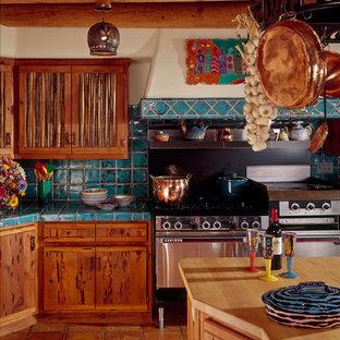 Mediterrane Küche mit flächenbündigen Schrankfronten, Schränken im Used-Look, Küchenrückwand in Blau, Küchengeräten aus Edelstahl und braunem Boden in Phoenix