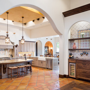 Mediterranean eat-in kitchen photos - Example of a tuscan u-shaped terra-cotta floor and orange floor eat-in kitchen design in Austin with a farmhouse sink, recessed-panel cabinets, light wood cabinets, multicolored backsplash, mosaic tile backsplash, stainless steel appliances, an island and beige countertops
