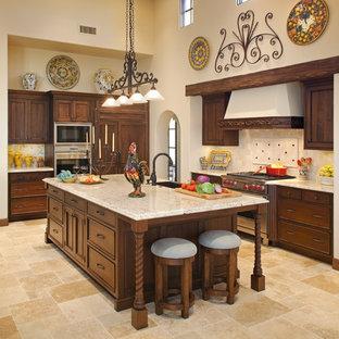 Idéer för mycket stora vintage kök, med luckor med infälld panel, skåp i mörkt trä, beige stänkskydd, integrerade vitvaror, en rustik diskho, kalkstensgolv, granitbänkskiva, flera köksöar och stänkskydd i kalk