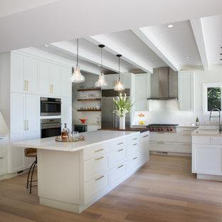 Diseño de cocina clásica renovada, grande, con armarios estilo shaker, puertas de armario blancas, salpicadero blanco, electrodomésticos de acero inoxidable, suelo de madera clara, una isla, suelo beige y encimeras blancas