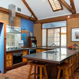ブリスベンの地中海スタイルのおしゃれなキッチン (一体型シンク、フラットパネル扉のキャビネット、ステンレスカウンター、マルチカラーのキッチンパネル、シルバーの調理設備、テラコッタタイルの床、赤い床、グレーのキッチンカウンター) の写真