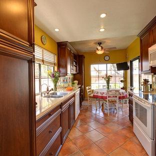 Неиссякаемый источник вдохновения для домашнего уюта: отдельная, параллельная кухня в средиземноморском стиле с фасадами с утопленной филенкой, фасадами цвета дерева среднего тона, столешницей из кварцевого композита, зеленым фартуком, фартуком из керамической плитки, полом из терракотовой плитки, розовым полом и бежевой столешницей
