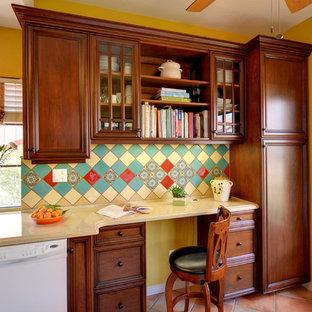 サンディエゴの地中海スタイルのおしゃれなキッチン (落し込みパネル扉のキャビネット、中間色木目調キャビネット、クオーツストーンカウンター、緑のキッチンパネル、セラミックタイルのキッチンパネル、テラコッタタイルの床、ピンクの床、ベージュのキッチンカウンター) の写真