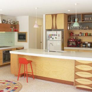 50 tals inredning av ett kök med öppen planlösning, med en undermonterad diskho, släta luckor, skåp i ljust trä, grönt stänkskydd, stänkskydd i tunnelbanekakel, vita vitvaror och en köksö