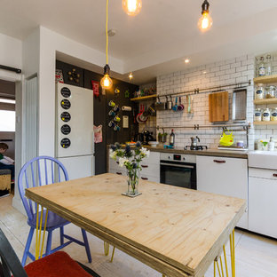 Photo of a small bohemian kitchen/diner in London with light hardwood flooring.