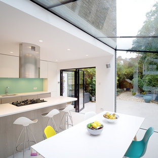 Design ideas for a scandinavian kitchen/diner in London with a submerged sink, flat-panel cabinets, white cabinets, blue splashback, an island, grey floors and white worktops.
