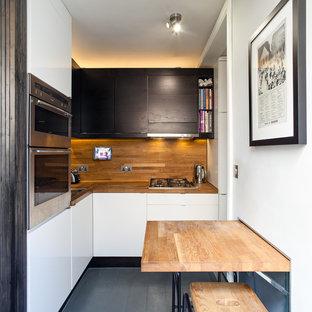 Пример оригинального дизайна интерьера: маленькая угловая кухня-гостиная в современном стиле с накладной раковиной, плоскими фасадами, черными фасадами, столешницей из дерева, коричневым фартуком, фартуком из дерева, техникой из нержавеющей стали, деревянным полом, полуостровом, серым полом и коричневой столешницей