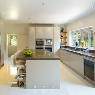 This is an example of a contemporary galley kitchen/diner in Hertfordshire with a double-bowl sink, flat-panel cabinets, grey cabinets, stainless steel appliances, an island, composite countertops and porcelain flooring.