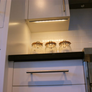 This is an example of a small modern galley eat-in kitchen in New York with an undermount sink, flat-panel cabinets, white cabinets, solid surface benchtops, subway tile splashback, stainless steel appliances, ceramic floors and with island.