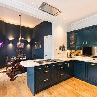 Diseño de cocina comedor en U, moderna, de tamaño medio, con fregadero encastrado, armarios estilo shaker, puertas de armario azules, encimera de acrílico, salpicadero con efecto espejo, electrodomésticos de acero inoxidable, suelo de madera clara, península y encimeras blancas