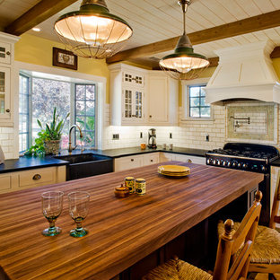 This is an example of a mid-sized beach style l-shaped eat-in kitchen in Santa Barbara with a farmhouse sink, beaded inset cabinets, white cabinets, wood benchtops, white splashback, subway tile splashback, black appliances, porcelain floors and with island.